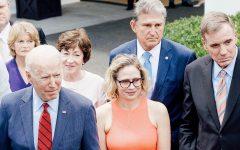 President Joe Biden stands with a bipartisan groups of Senators, including Senator Sinema (bottom center) and Joe Manchin (top center) (Win McNamee/Getty Images)