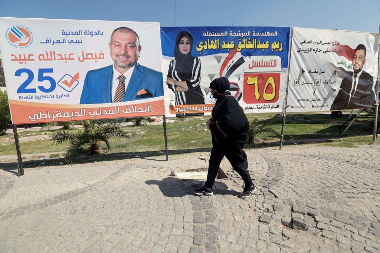 A woman in Baghdad strolls past campaign posters before the parliamentary election on October 10 [Wissam al-Okaili/Reuters]